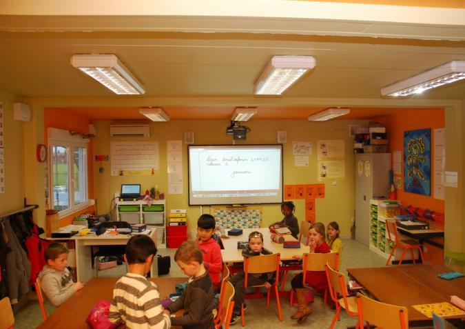 Kinderen in een klas met aan het plafond spiegelreflectie-armaturen.