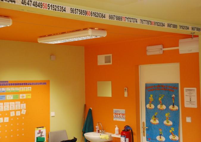 Witte plafonds in een oranje klaslokaal
