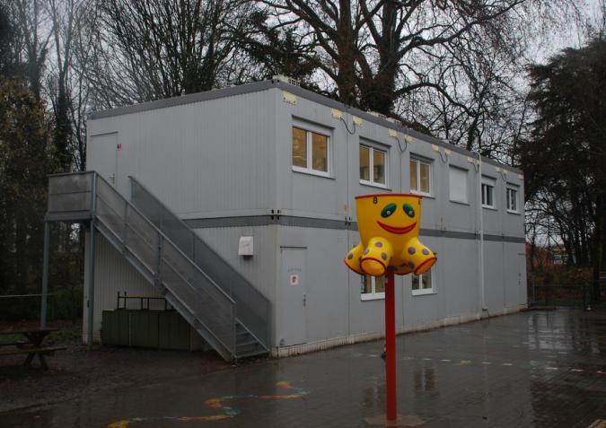 Herbruikbaar gebouw met een buitentrap aan een speelplaats
