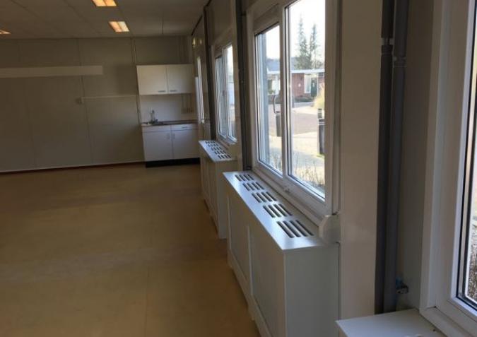 Radiators met beschermende omkasting onder de ramen van een klas