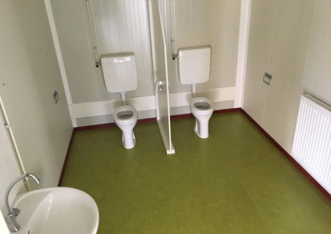 Twee toiletten voor volwassenen in deze containerklas