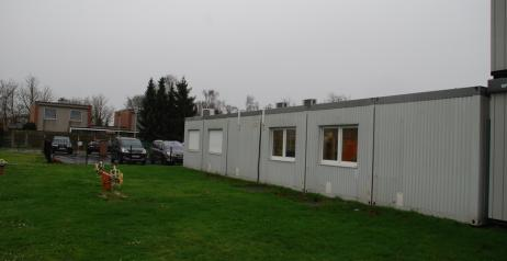 Buitenaanzicht van een modulaire klas aan een grasveld